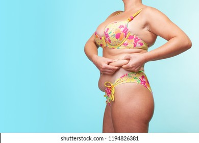 asian fat women has overweight. sagging skin. she used hands squeezing excess fat of the waist. blue background. girl wants lose weight. concept of surgery and subcutaneous fat breakdown. steed image