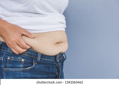 Asian fat women has overweight in jeans. woman's hand holding excessive belly fat isolated on gray background. concept of surgery and subcutaneous fat breakdown.