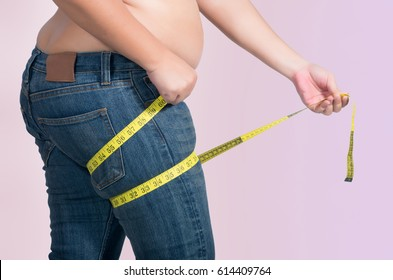 asian fat women has overweight. she measuring legs girth with measure tape. isolated on violet background. she wants lose weight. concept of surgery and subcutaneous fat breakdown.