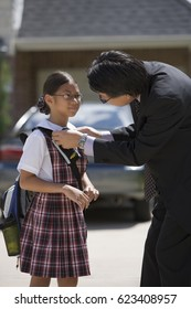 Asian father adjusting daughter's school uniform outdoors