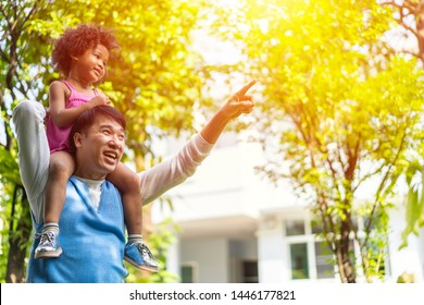 Asian father and Adopted child or daughter  on nature on sunset, diversity family or mixed race Parents Carrying kid On Shoulders As They Walk In Park. concept of Happy family spending good time