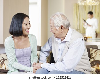 asian father and adult daughter chatting on couch