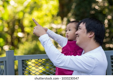 Asian Father carrying daughter and pointing to learning in the deep forest, Family and Homeschooling concept