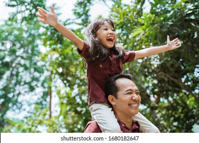 asian father carrying on neck smiling daughter while walking in the park