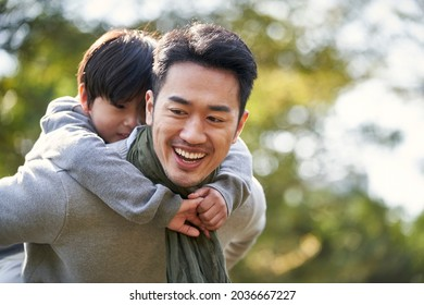 asian father carrying son on back having fun outdoors in park