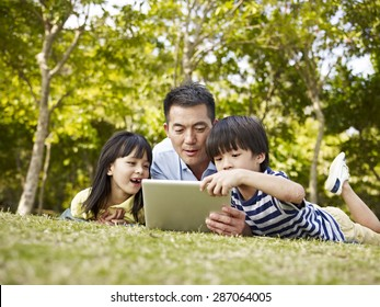 asian father and children lying on grass looking at tablet computer in a park.