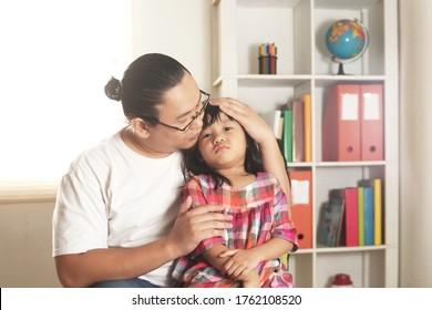 Asiatischer Vater beruhigt ihre traurige und weinende Tochter, Alleinvater und Mädchen zusammen
