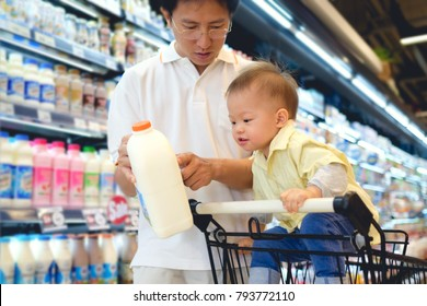 Asian Father & Cute little 18 months old toddler boy child choosing milk product in grocery store, Dad read milk nutrition facts with child sit in shopping cart, Kid first experience concept