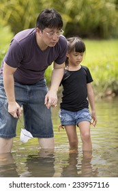 Asian father and daughter bonding time catching fishes in river