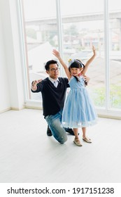 An Asian father and daughter are dancing, dad teaches daughters to dance in a fun room.