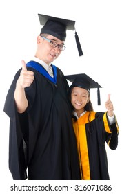 Asian father and daughter in graduation gown and raised their thumbs up