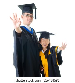 Asian father and daughter in graduation gown and making okay sign