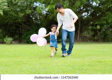 Asian father and daughter are playing the balloons and they running and laughing together with fully happy moment in the park, concept of outdoor activity in family lifestyle.