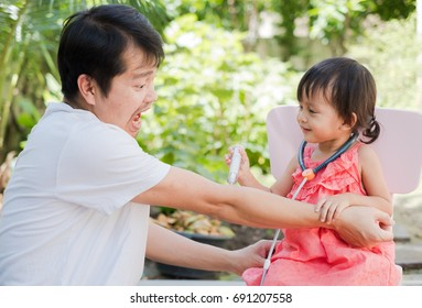 Asian father and daughter playing together with happy and funny moment, they playing a role of doctor and patient, concept of learning by playing for toddler development.