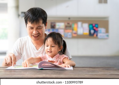 Asian father and daughter are reading the storybook together and they are smiling with happy moment, concept of learning activity for kid in family lifestyle. And role of parent support to the child.