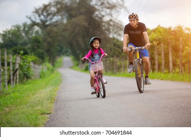 Asian father and daughter Riding bicycles on the street