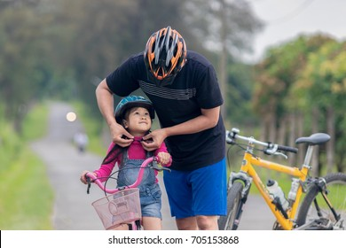 Asian father and daughter Riding bicycles on the street.Healthy lifestyle concept and father wears a bicycle helmet to his daughter .soft focus