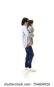 The Asian father and daughter walk along together on the white background.