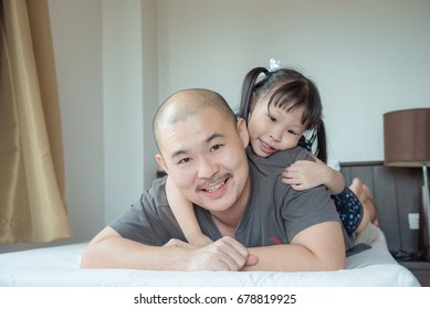 Asian father having fun with his cute little daughter, smiling and lying on bed
