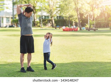 Asian father and his daughter stretching their arms and shoulders before exercising. Workouts and lifestyles concept. Happy family life and Health care concepts. Kid and dad having Fun with sport day.