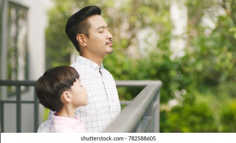 Asian father and his son standing on balcony enjoying fresh nature
