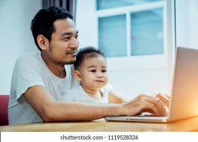Asian father and his son is using the laptop computer at their home on sunday or holiday.