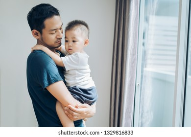 Asian father hold little son near window at home.