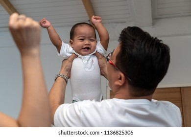 Asian father holding the boy baby Raising hands and mother hand in the house, Family Lifestyle Concept