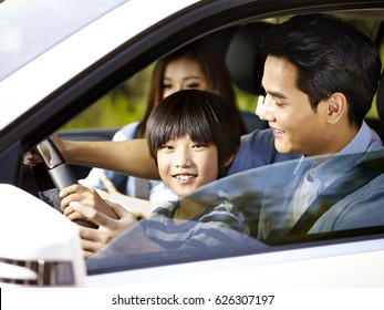 asian father letting his son hold the steering wheel of his car.