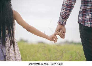 Asian father and little cute daughter playing together in park,Dad holding hands's daughter with love,I love you Dad,green rice field background.Daddy and Family Day Concept.