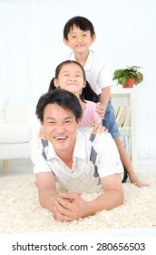 Asian father piggyback his children