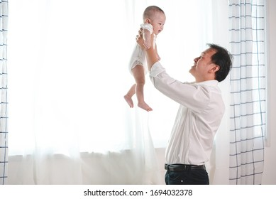 Asian father playing with her baby to fly in white bedroom the baby smile and laugh with happy and funny. fatherhood, dad and kids, healthy of children, family relationship concept.
