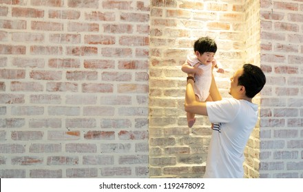 Asian Father raises he baby hands up