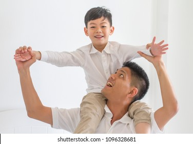 Asian father and son happy little boy stretching out hands while his father carrying him on shoulders.