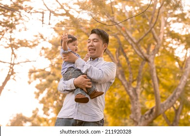 Asian father and son having fun outdoors in autumn