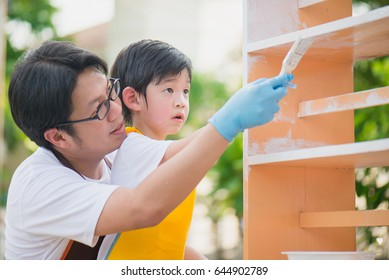 Asian father and son painting wooden shelf together