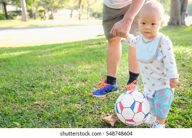 Asian Father and son play football in the park at day time. Dad teach his toddler boy to kick soccer, Dad and baby boy son holding hand, Concept of friendly family. Kid first experience - warm tone