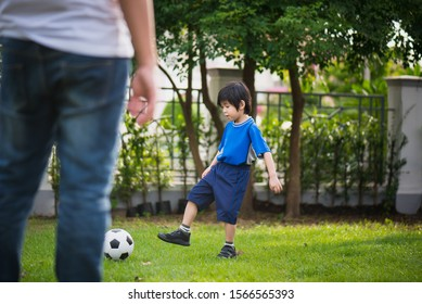 Asian father Father and son playing football in the garden