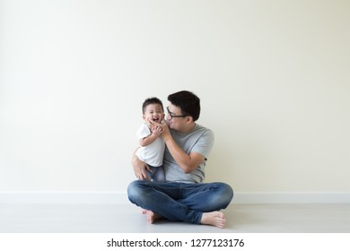 Asian father and son playing and smiling on floor in the room, Family having fun and laughs concept