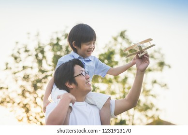 Asian father and son playing wooden airplane together in the park outdoors