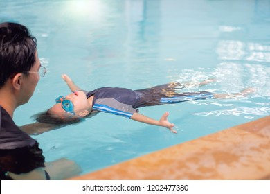 Asian Father take Cute little Asian 30 months / 2 years old toddler baby boy to swimming class in Thailand, Kid learn to float with dad at indoor salt water pool, Parent teach child back floating