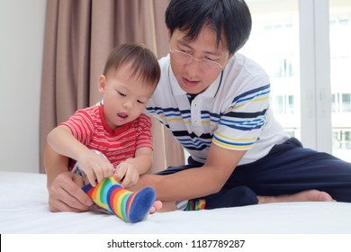 Asian father teaching cute little Asian 2 years old toddler boy child putting on his own socks, Dad and son sitting on bed concentrate on wearing socks, Encourage Self-Help Skills in Children concept