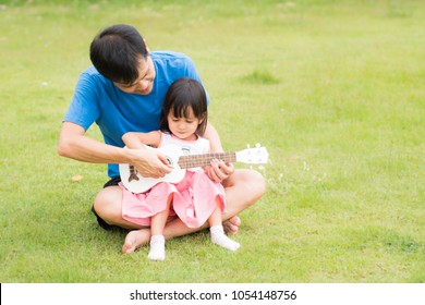 Asian father is teaching his daughter to play ukulele and the girl is singing the song together with him with fully happiness moment, concept of music education for kid in family lifestyle.