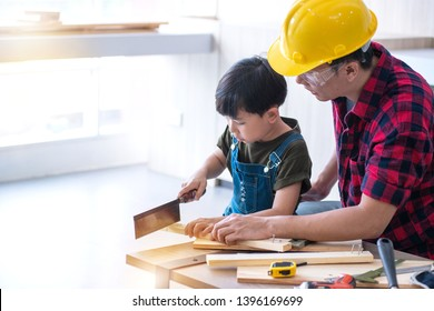 Asian father teaching kid son to use tools. son helping dad with building work at their home