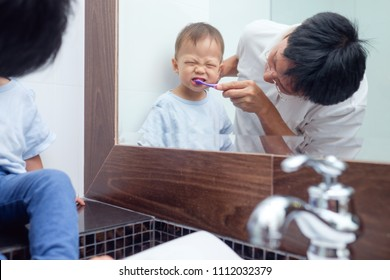 Asian Father teaching kid teeth brushing, Cute little 18 months / 1 year old toddler boy child brushing teeth & look in mirror with dad in bathroom, Tooth care for children, Child development concept