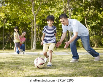 asian father teaching son to play soccer (football) in a park while mother and daughter watching from behind.