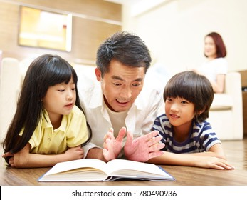 asian father and two children lying on front on floor reading book while mother watching in the background.