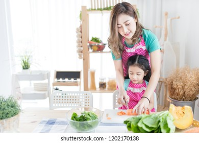 Asian femail and asian children cooking organic salad, they use knife cut fresh carrot on chopping board, asian children  learning to cook in kitchen room, family activity