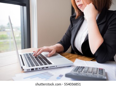 Asian female accountant or banker making calculations. Savings, finances and economy concept through a laptop.