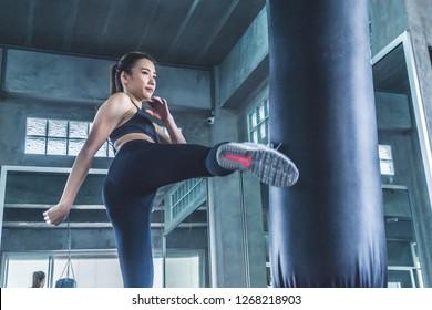 Asian female athlete in sportswear kicking sandbag in the gym.